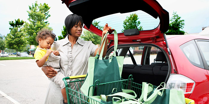 woman with baby puts groceries into a car