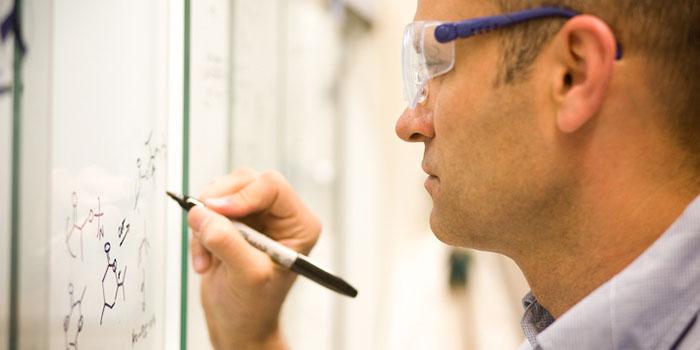 scientist diagrams on a white board