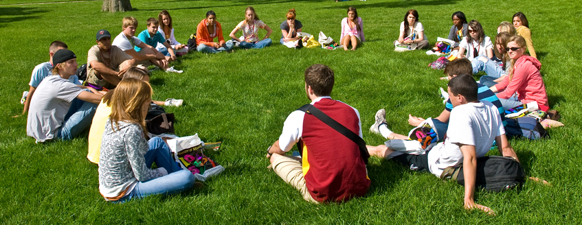 Group of students seated on grass in a circle