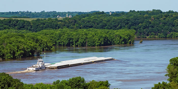 A tug pushes barges against the current of the Mississippi River near Sabula, Iowa.