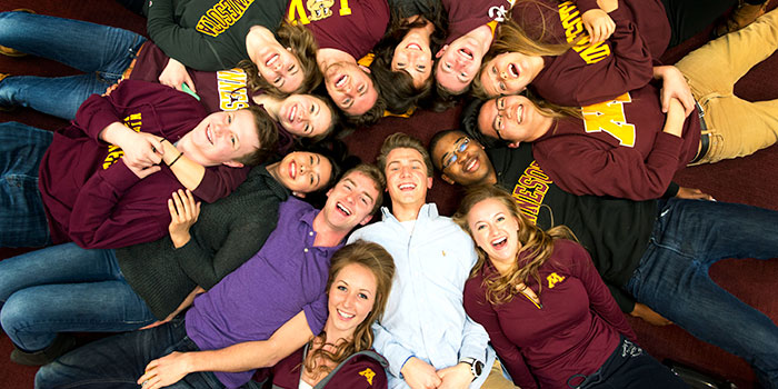 UMN students lying in a circle smiling up at the camera
