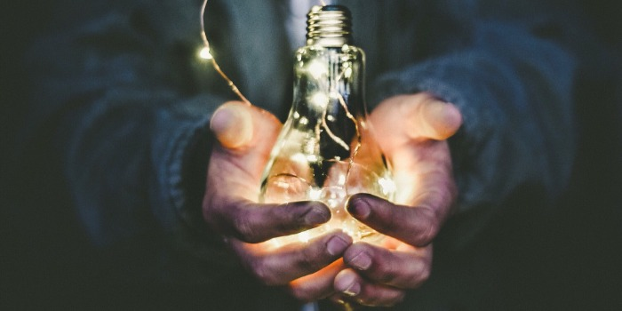 a persons hands hold a lightbulb filled with small twinkle lights