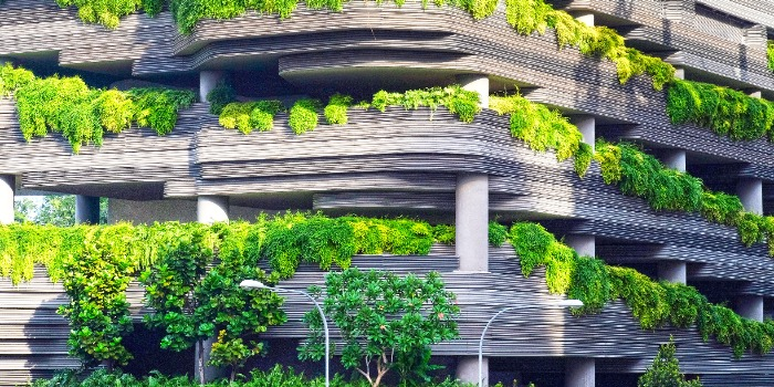 a multi-level parking structure with many green plants growing on each level