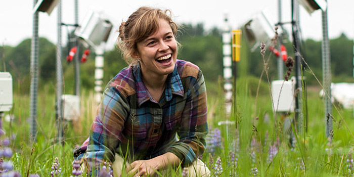Clare Kazanski sits in a field with measuring instruments