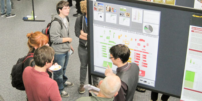 A group of students talk with a presenter at the Sustainability Symposium