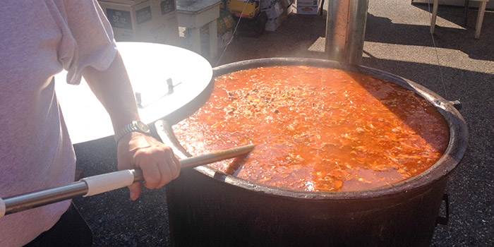 the chef stirs the big pot of booya