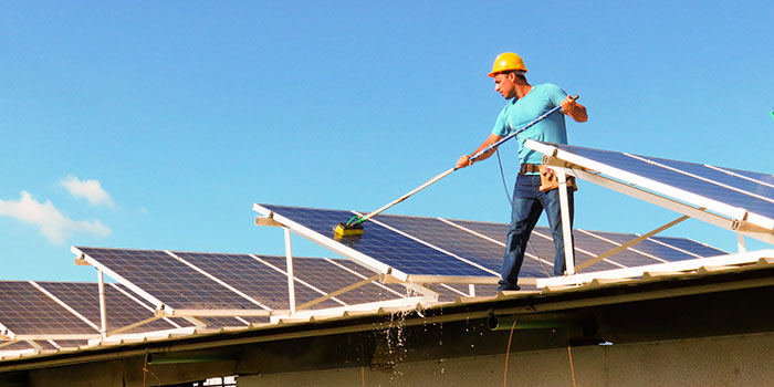 A worker cleans a photovoltaic solar panel