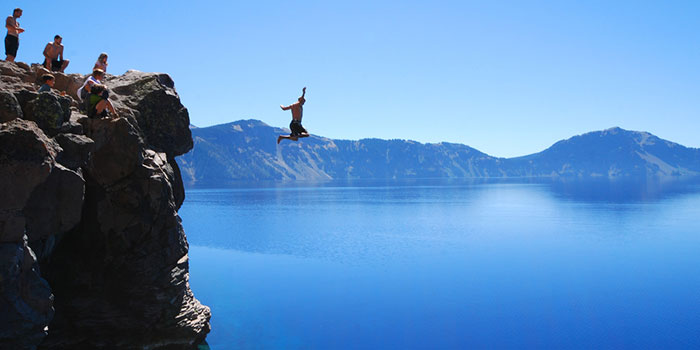 People standing on cliff jumping into big blue Crater lake