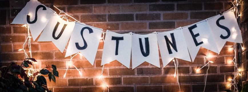 Sign reading SUSTUNES with twinkly lights against a brick wall