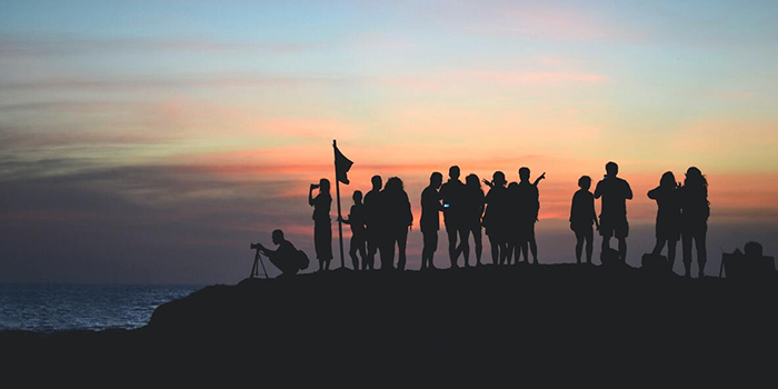 A group of people in silhouette watch the sunrise.
